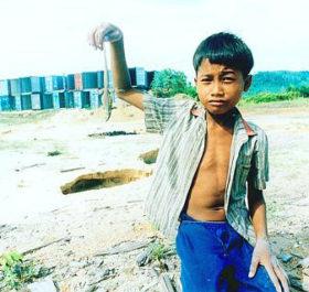 Một bé trai chơi gần nơi đặt các thùng container chứa chất thải của Formosa tại Sihanoukville. Ảnh tư liệu: BAN