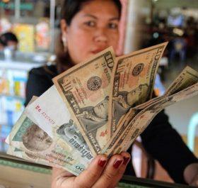 Một người dân cầm giấy bạc USD và riel của Campuchia - Ảnh: Reuters